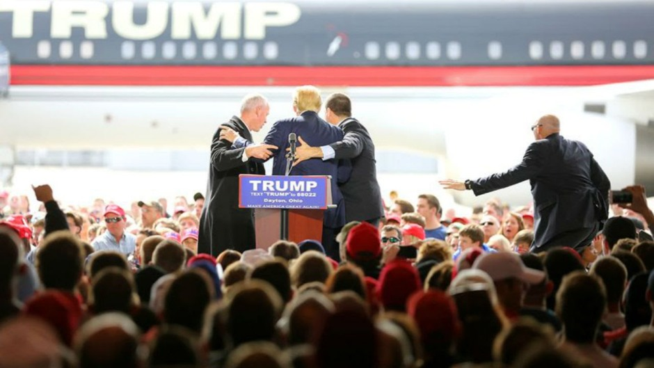 Personal de seguridad rodea al precandidato presidencial republicano Donald Trump después de que un hombre intentó subirse al escenario durante un mitin de campaña en Vandalia, Ohio, en las afueras de Dayton, el sábado 12 de marzo de 2016. El hombre fue detenido y Trump continuó con su discurso. (Carrie Cochran/The Cincinnati Enquirer vía AP)