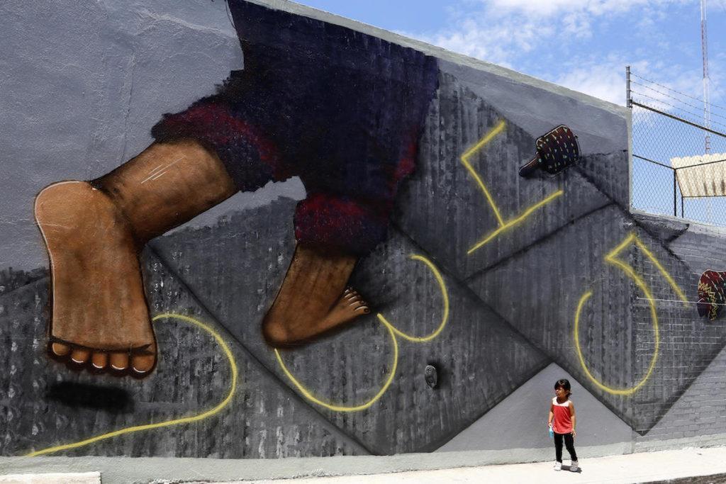"""ACOMPAÑA CRÓNICA: MÉXICO ARTE MEX06. XANENETLA (MÉXICO), 02/04/2016.- Fotografía del 31 de marzo de 2016 de una niña frente a un mural del grupo de artistas Colectivo Tomate en el barrio de Xanenetla en la ciudad de Puebla (México). El barrio de Xanenetla, considerado como uno de los más """"bravos"""" de la ciudad de Puebla (centro de México), ha sido por años epicentro de crímenes y delitos; sin embargo, la colina ha sufrido una transformación gracias al arte. EFE/Francisco Guasco"""