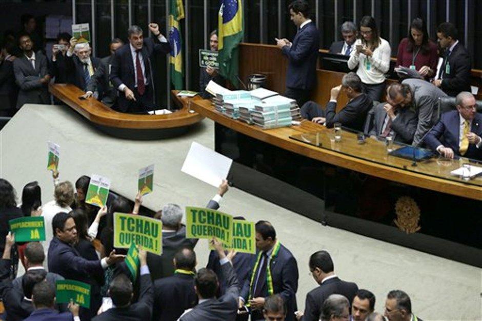 """El Fiscal General de Brasil, José Eduardo Cardozo, arriba a la izquierda, defiende a la presidenta de Brasil, Dilma Rousseff, en la Cámara de Diputados, mientras que líderes de oposición sostienen pancartas que en portugués dicen """"Adiós querida"""" y """"Juicio Político Ya"""" en Brasilia, Brasil, el viernes 15 de abril de 2016. (AP Foto/Eraldo Peres)"""