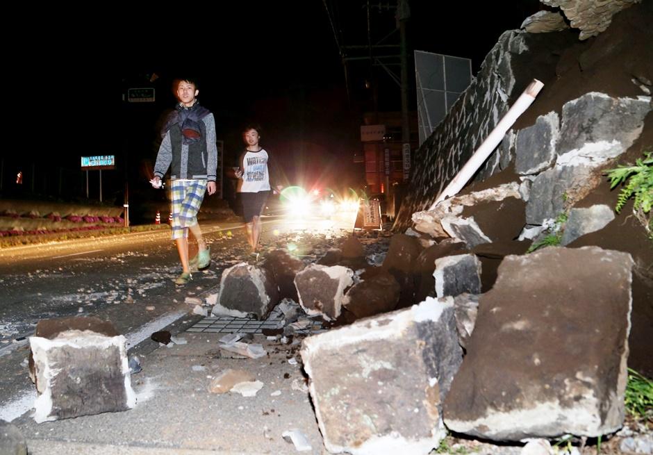Personas caminan junto a las paredes colapsadas a causa de un terremoto en la población de Mashiki, en Kumamoto, en el sur de Japón el jueves 14 de abril de 2016. Un potente terremoto de magnitud 6,5 derribó viviendas en el sur de Japón la noche del jueves, y la policía reportó que podría haber personas atrapadas entre los escombros. (Kyodo News via AP)