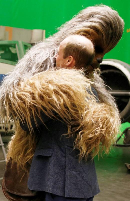 El príncipe Guillermo de Gran Bretaña recibe un abrazo del personaje Chewbacca durante una visita al plató de Star Wars en los estudios Pinewood, el martes 19 de abril del 2016 en Iver Heath, en el oeste de Londres. (Adrian Dennis/Pool vía AP)