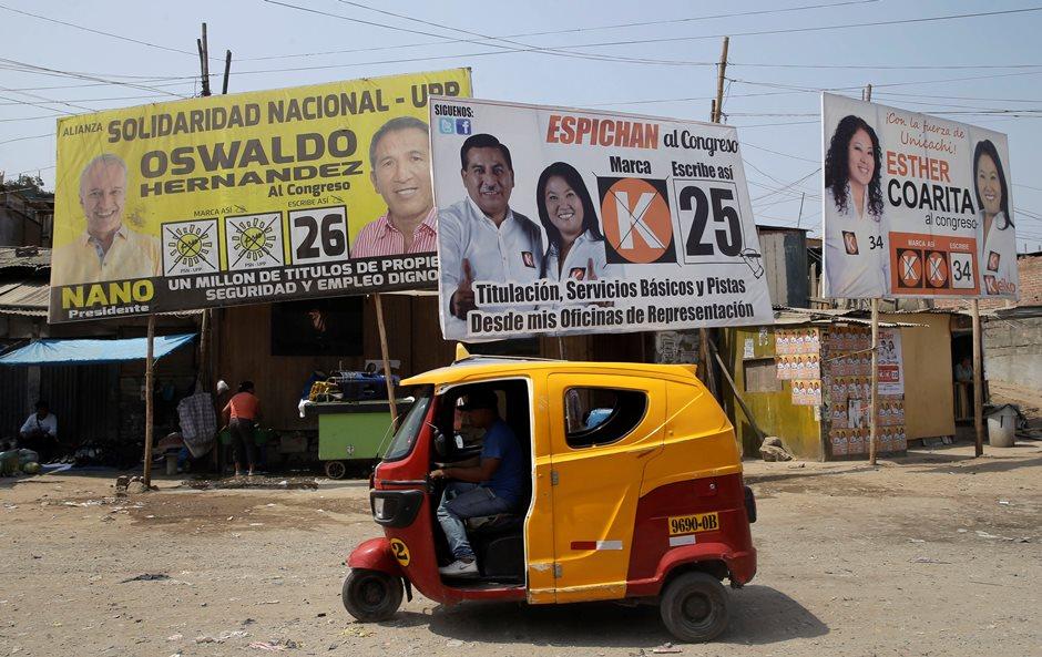 Carteles propagandísticos de la candidata a la presidencia Keiko Fujimori, en el centro derecha, y al candidato al congreso Oswaldo Hernandez, a la izquierda, en una barriada de Lima, Perú, el sábado 9 de abril de 2016. (AP Foto/Martin Mejia)