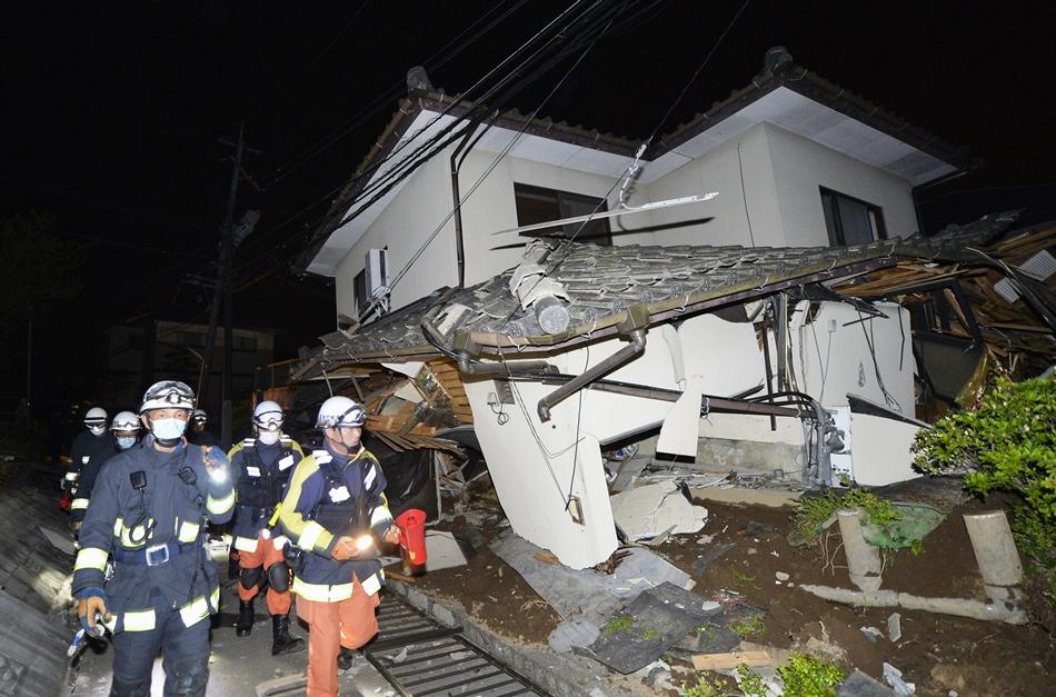 Bomberos revisan los daños en una casa colapsada en Mashiki, cerca de la ciudad de Kumamoto, en el sur de Japón, luego de un terremoto la mañana del viernes 15 de abril de 2016. Los rescatistas en el sur de Japón buscaban a residentes atrapados entre los escombros de al menos una docena de casas que colapsaron luego de que el potente terremoto de magnitud 65 azotara el jueves con tal fuerza que interrumpió los servcios de agua y electricidad. (Tomoaki Ito/Kyodo News via AP)