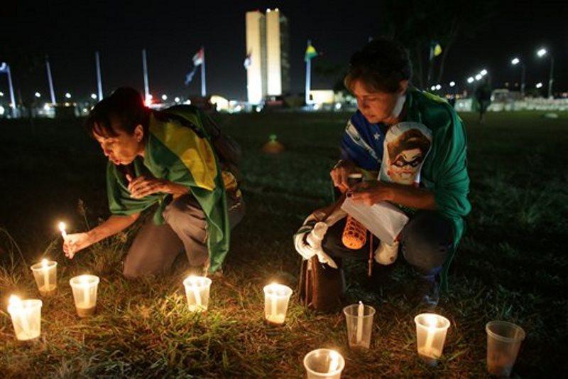 Manifestantes contrarios al gobierno encienden velas ante el Congreso brasileño, donde los legisladores debaten si impugnar a la presidenta, Dilma Rousseff, en Brasilia, Brasil, el sábado 16 de abril de 2016. (AP Foto/Eraldo Peres)