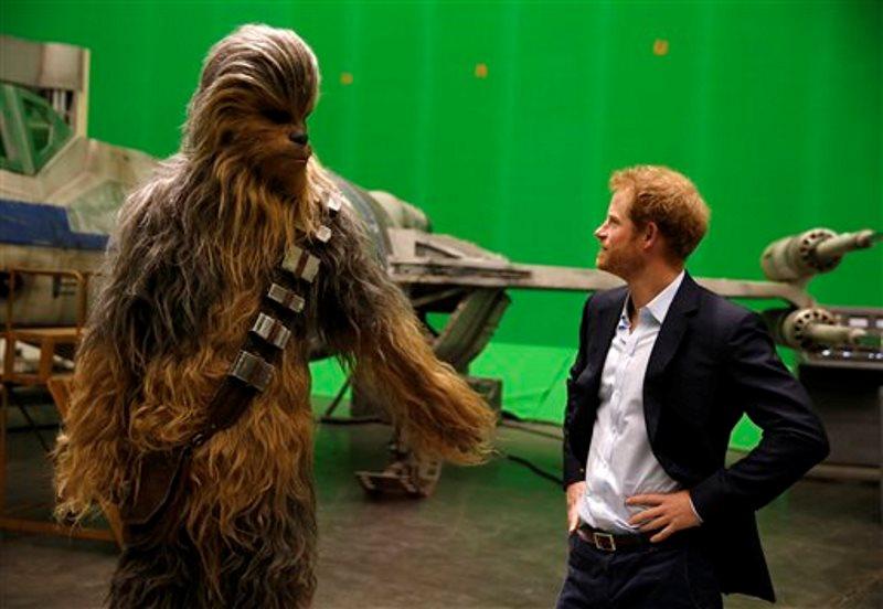 El príncipe Enrique de Gran Bretaña conoce al personaje de Chewbacca durante una visita al plató de Star Wars en los estudios Pinewood, el martes 19 de abril del 2016 en Iver Heath, en el oeste de Londres. (Adrian Dennis/Pool vía AP)