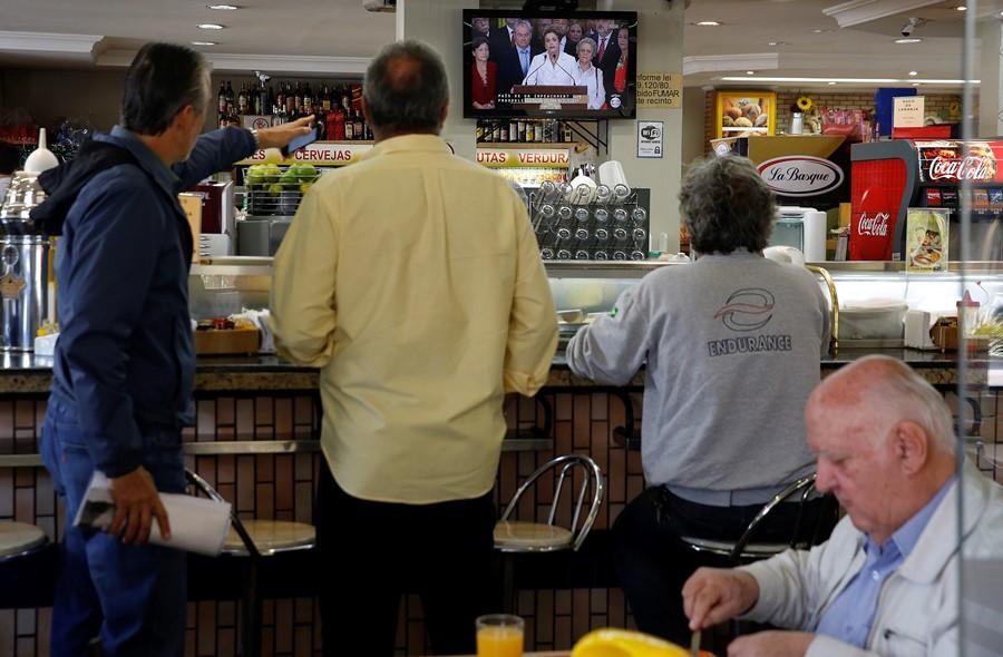 Brasileños en restaurantes observan el discurso pronunciado por la suspendida presidenta Dilma Rousseff en Sao Paulo, Brasil, el jueves 12 de mayo de 2016.. (AP Foto/Andre Penner)