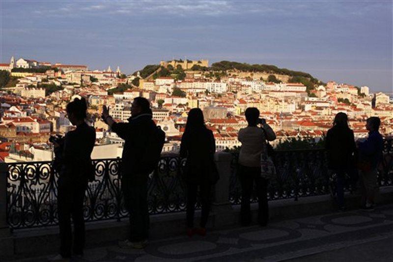 En la imagen, la silueta de varios turistas haciendo fotos al centro de Lisboa al sol del atardecer. (AP Foto/Armando Franca)