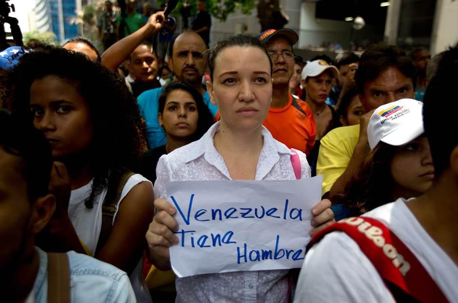 """Una mujer sostiene un cartel que dice """"Venezuela tiene hambre"""" durante una manifestación de la oposición en apoyo a una referendo revocatorio del mandato del presidente Nicolás Maduro, en Caracas, Venezuela, el miércoles 25 de mayo de 2016. (Foto AP / Ariana Cubillos). (AP Photo/Fernando Llano)"""
