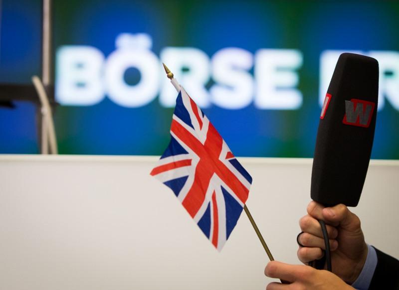 El presentador de un programa de noticias financieras sostiene una bandera británica mientras informa desde la Bolsa de Fráncfort, Alemania, el viernes 24 de junio de 2016. (Frank Rumpenhorst/dpa via AP)