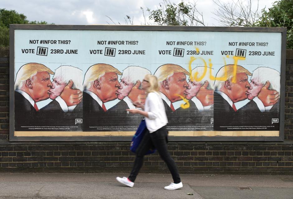 Una mujer camina frente a carteles a favor de votar por la permanencia de Gran Bretaña en la Unión Europea, en Londres, 21 de juniio de 2016. En el cartel aparece el candidato republicano estadounidense Donald Trump besando al principal partidario de la salida británica, Boris Johnson. (Yui Mok / PA via AP)