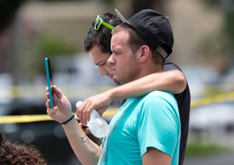 Una pareja lloran a las victimas del tiroteo en el club de Orlando, en las mediaciones de dicho club gay. GREGG NEWTON (AFP)