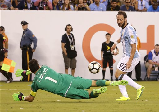 El jugador de la selección de Argentina, Gonzalo Higuaín, derecha, remata y falla un gol ante el arquero de Chile, Claudio Bravo, en la final de la Copa América Centenario el domingo, 26 de junio de 2016, en East Rutherford, Nueva Jersey. (AP Photo/Frank Franklin II)