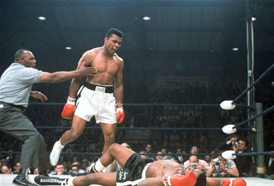 ARCHIVO - En esta imagen de archivo del 25 de mayo de 1965, el campeón de peso completo Muhammad Ali es retenido por el árbitro Joe Walcott, a la izquierda, después de que Ali noqueara a su rival Sonny Liston en el primer asalto de su combate por el título en Lewiston, Maine. Ali, el indómito campeón peso completo cuyos demoledores golpes y avasalladora personalidad transformaron el deporte y le hicieron una superestrella mundial, ha fallecido, informó su familia. Tenía 74 años. (AP Foto/Archivo)