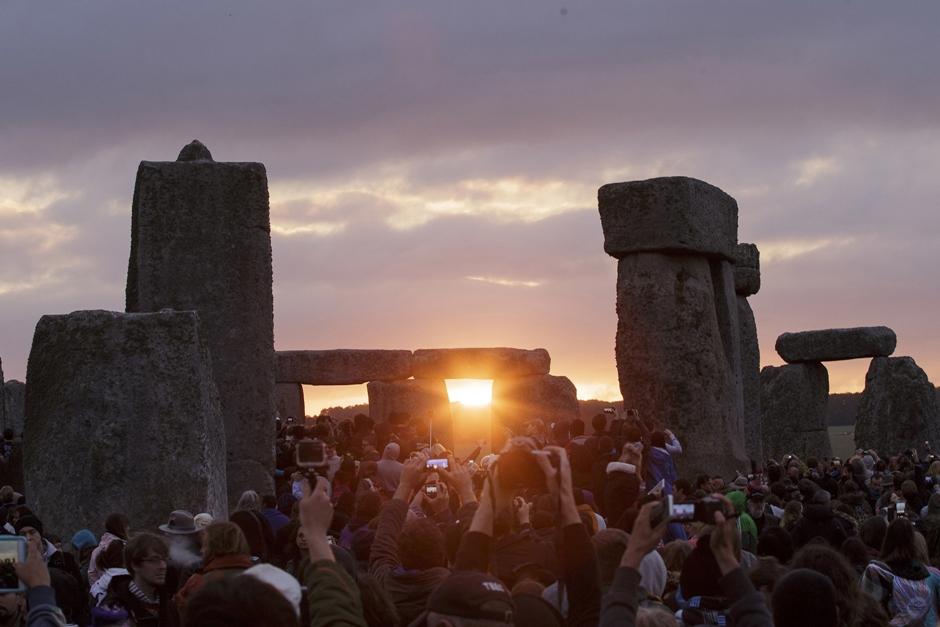 En esta fotografía de archivo del 21 de junio de 2015, el sol sale cuando miles de espectadores se reúnen en Stonehenge para celebrar el solsticio de verano, el día más largo del año, cerca de Salibury, Inglaterra. (AP Foto/Tim Ireland, Archivo). )