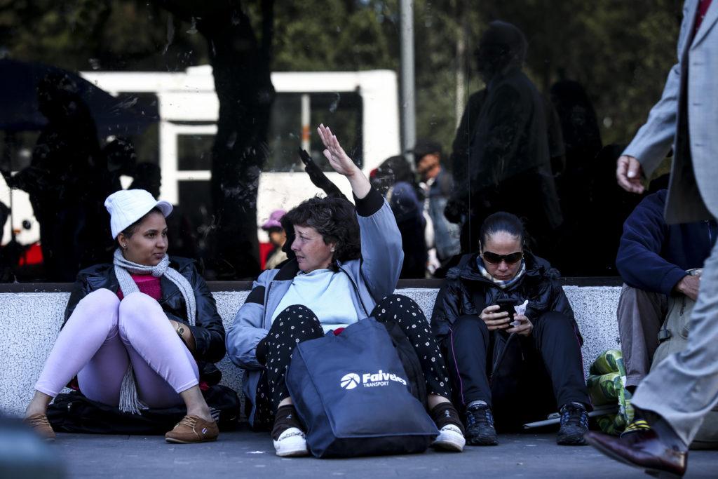 QUITO (ECUADOR), 06/07/2016.- Ciudadanos cubanos esperan a sus compatriotas en las afueras de la Unidad de Flagrancia hoy, miércoles 6 de julio de 2016, en Quito (Ecuador). La Policía desalojó hoy a decenas de cubanos que estaban acampando en un parque público de Quito y que reclaman visas para llegar a México para, desde ahí, ir a EEUU. EFE/José Jácome