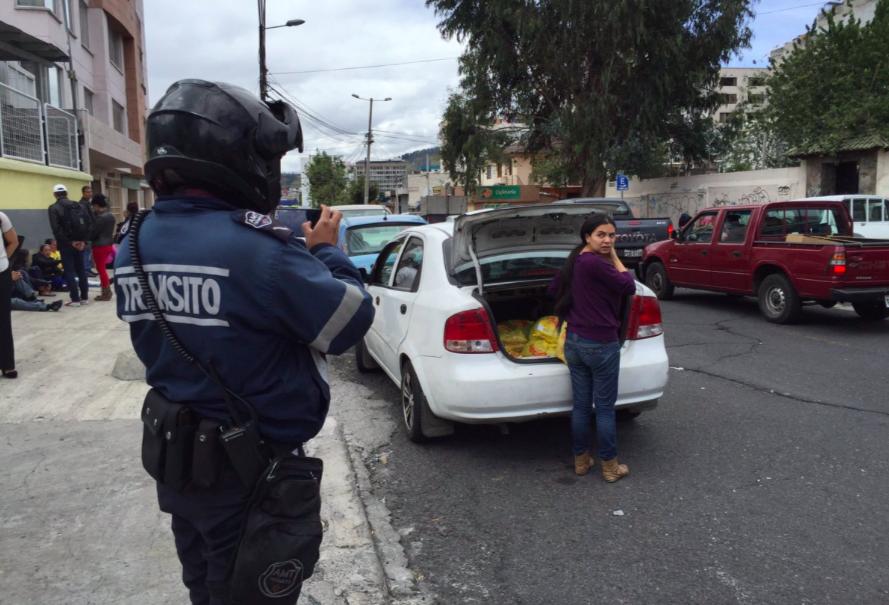 Oficial de la Policía fotografiando a mujer que fue a donar comida a familiares de cubanos detenidos en Hotel Carrión. Foto de Daniela Salazar.