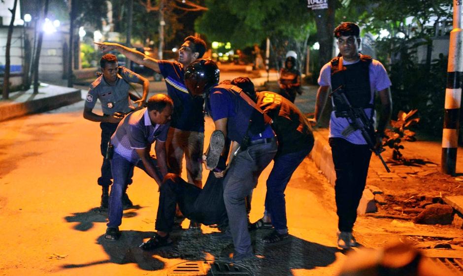 Un grupo de personas ayudan a un herido después que hombres armados atacaron un restaurante popular entre los extranjeros en una zona diplomática de Daca, la capital de Bangladesh, el viernes 1 de julio de 2016, donde tomaron rehenes e intercambiaron disparos con fuerzas de seguridad. (AP Foto)