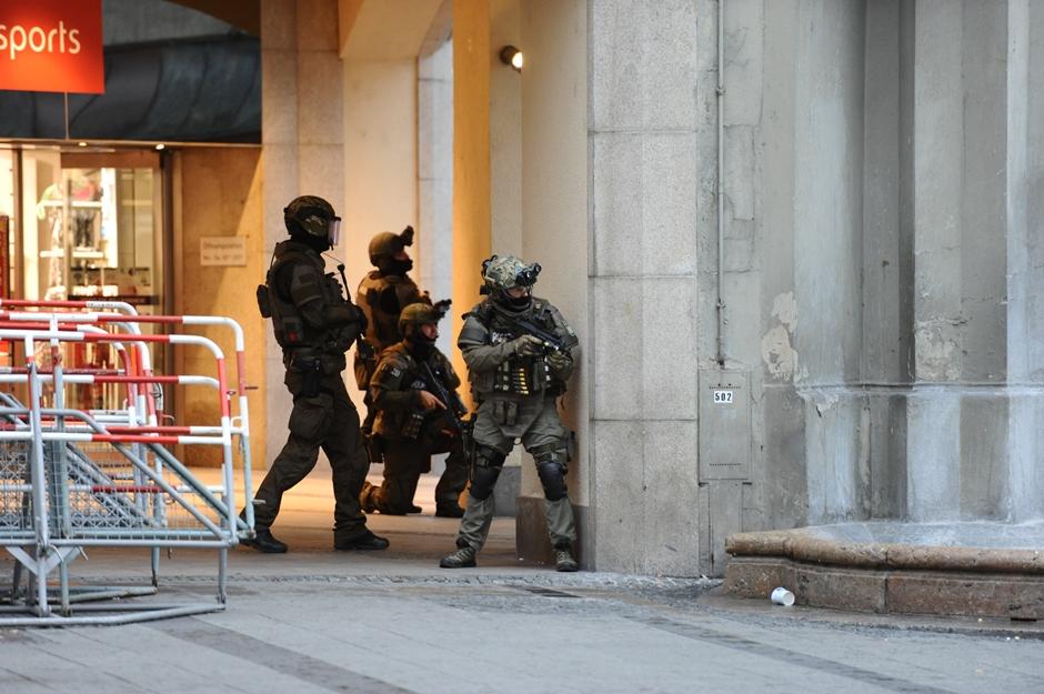 Policías fuertemente armados se parapetan en la plaza Karlsplatz (Stachus), en Munich, Alemania, luego de un tiroteo en el centro comercial Olympia que causó al menos seis muertos y varios heridos. el viernes, 22 de julio del 2016. (Andreas Gebert/dpa via AP)