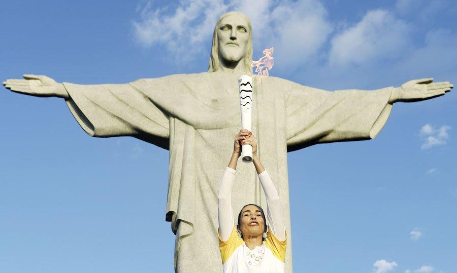 La exjugadora de voleibol brasileña Isabel Barroso Salgado lleva la antorcha olímpica hoy, viernes 05 de agosto de 2016, en el Cristo Redentor, en Río de Janeiro (Brasil). La inauguración de los Juegos Olímpicos se realizará hoy a las 20:00, hora local, en el Estadio Maracaná de Río. EFE / Fernando Maia