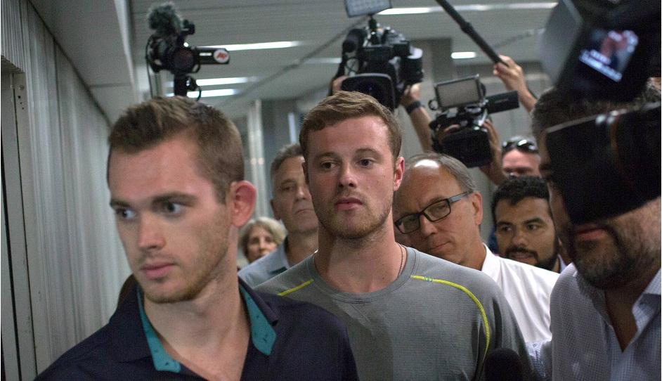 Los periodistas se reúnen en torno a los nadadores estadounidenses olímpicos Gunnar Bentz, izquierda, y Jack Conger, centro, mientras sales de una estación de policía en el aeropuerto internacional de Río de Janeiro, el jueves 18 de agosto de 2016. (AP Foto/Mauro Pimentel)