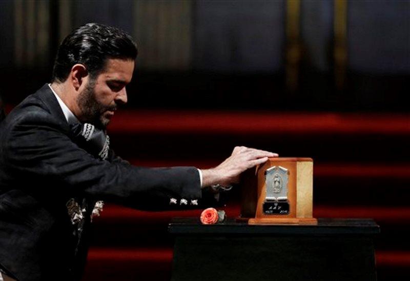 El cantante Pablo Montero toca la urna con las cenizas de Juan Gabriel para decir adiós al superastro de la música mexicana, el lunes 5 de septiembre del 2016 en el Palacio de Bellas Artes, en la Ciudad de México. (AP Foto/Rebecca Blackwell)