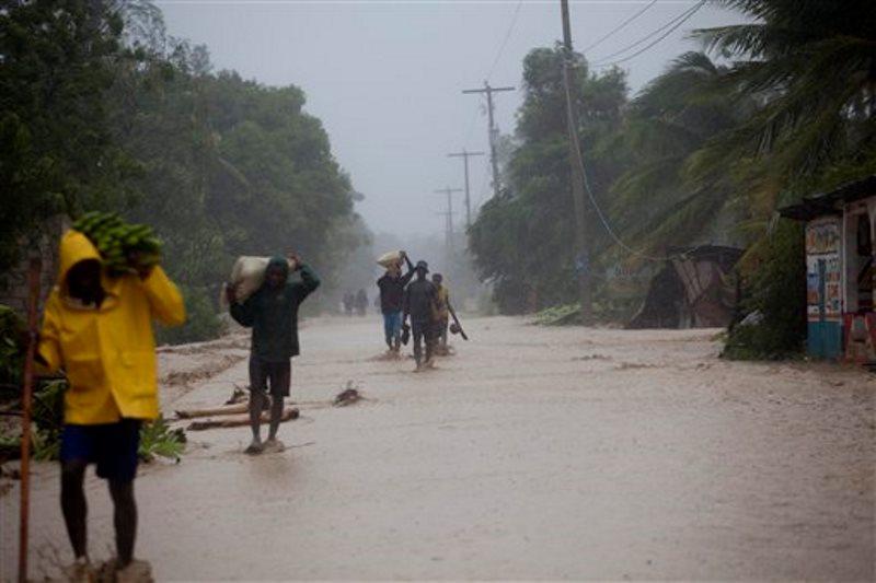 Varios residentes caminan en calles inundadas mientras regresan a sus casas en Leogane, Haití, el martes 4 de octubre de 2016, tras el paso del huracán Matthew. (AP Foto/Dieu Nalio Chery)