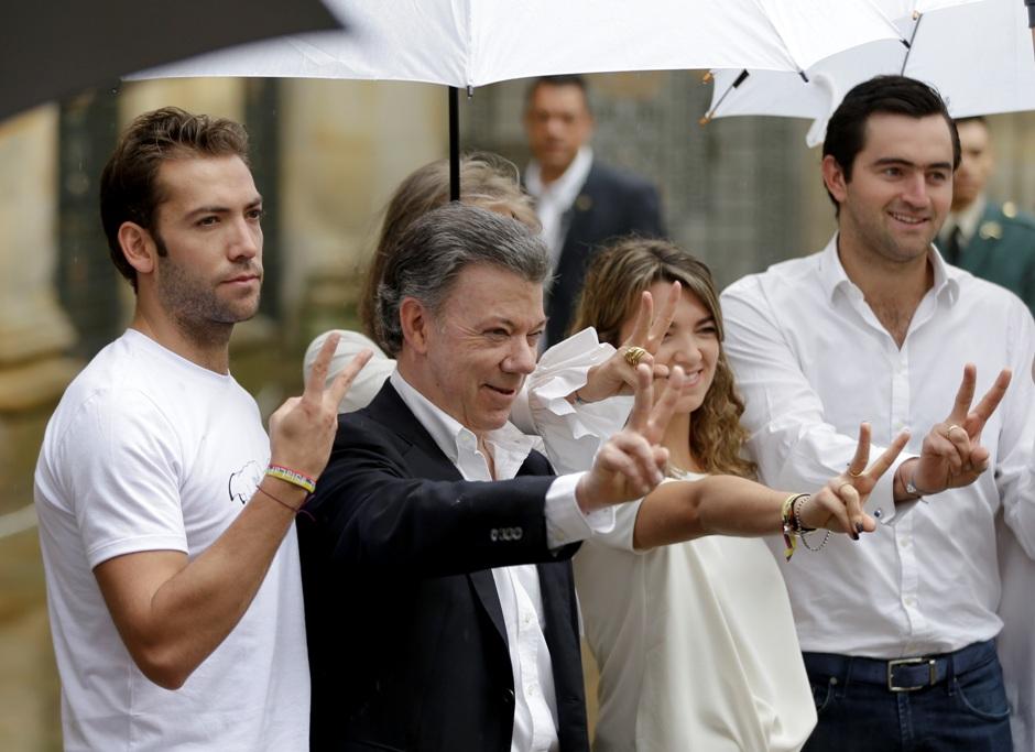 El presidente colombiano Juan Manuel Santos, 2do izquierda, flanqueado por su hijo Martín Santos, izquierda, y su hija Marian Antonia Santos, 3ra izquierda, hacen la V de la victoria luego de votar en el plebiscito sobre los acuerdos de paz entre el gobierno colombiano y las FARC, Bogotá, domingo 2 de octubre de 2016. (AP Foto/Ricardo Mazalan)