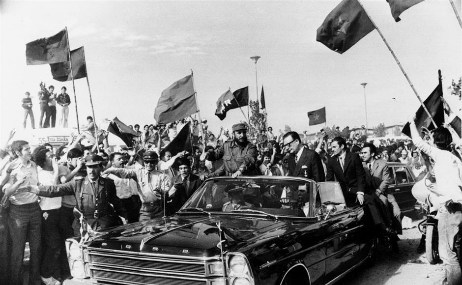 En esta fotografía del 10 de noviembre de 1971, el líder cubano Fidel Castro, centro izquierda, viaja acompañado por el presidente chileno Salvador Allende entre una multitud que ondea banderas comunistas en Santiago, Chile. Fidel Castro falleció el 25 de noviembre de 2016 a los 90 años. (Foto AP/Archivo)