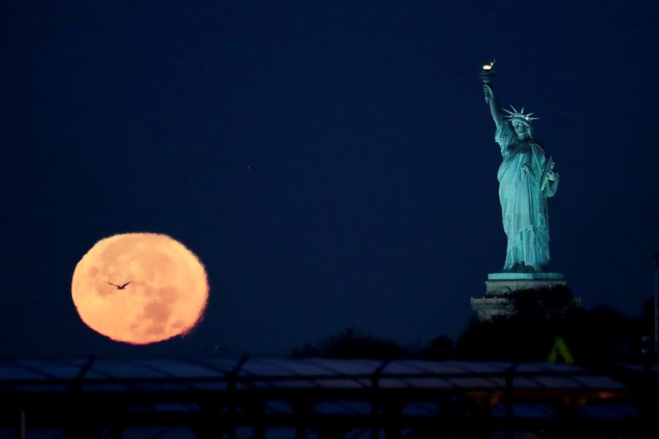 La Luna detrás de la Estatua de la Libertad, en las primeras horas del lunes 14 de noviembre de 2016, en Nueva York. (AP Foto/Julio Cortez)