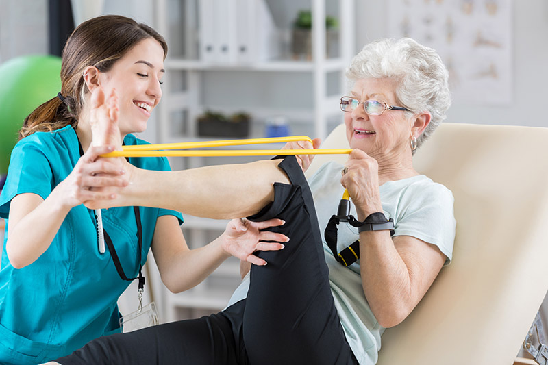 Physical therapist helps patient use resistance band