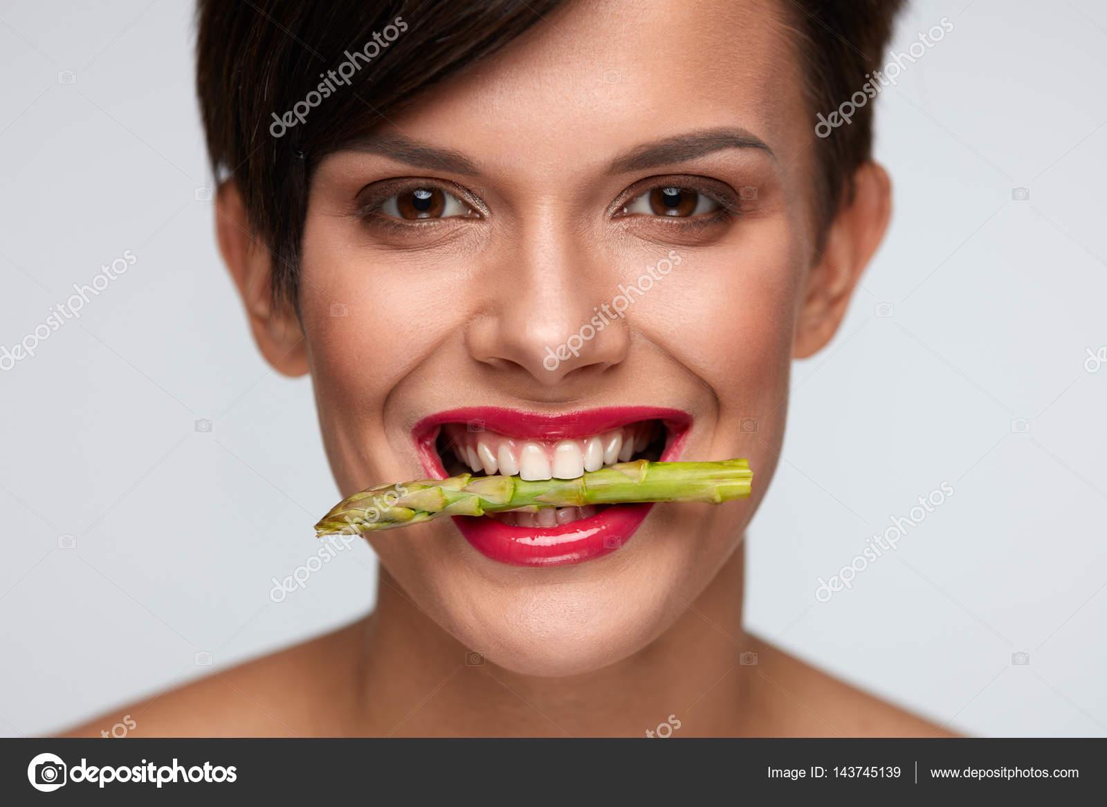Healthy Eating.  Beautiful Woman Holding Asparagus Between Teeth
